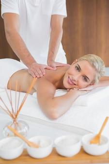 Mujer que recibe masaje de espalda en el centro de spa
