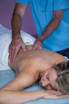 Mujer que recibe masaje de espalda de fisioterapeuta