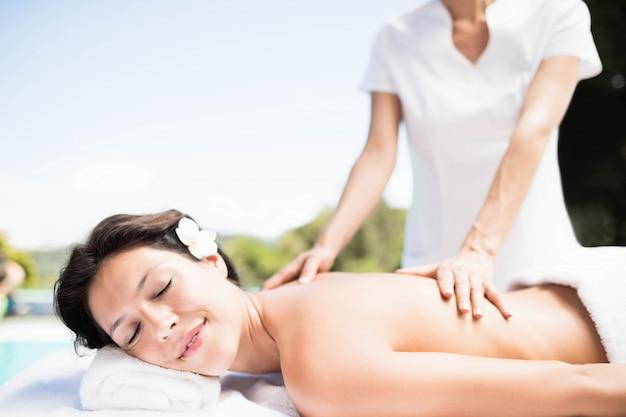 Mujer que recibe un masaje de espalda de masajista en un spa