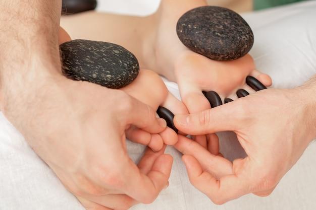 Mujer que recibe masaje con piedras calientes.