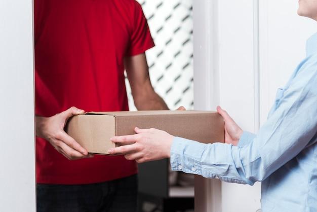 Mujer que recibe un paquete del primer plano de mensajería