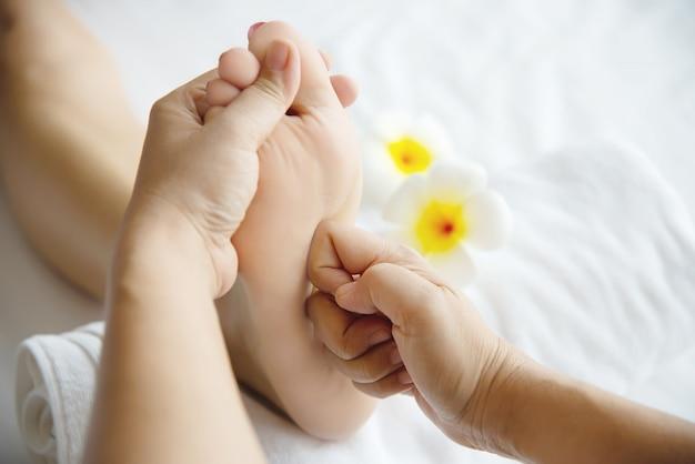 Mujer que recibe servicio de masaje de pies desde masajista de cerca a mano y pie - relájese en el concepto de servicio de terapia de masaje de pies