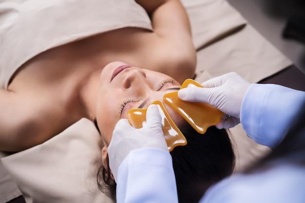 Mujer que recibe terapia facial tradicional de guasa