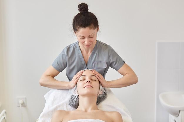 Mujer que recibe tratamiento de spa, cosmetóloga hace masaje facial para un cliente joven.