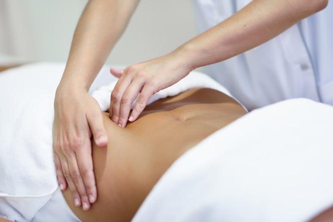 Mujer que recibe un masaje del vientre en el salón del balneario