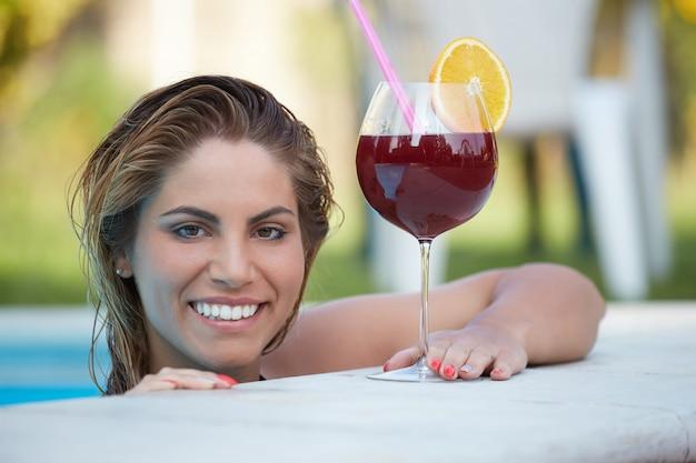 Mujer que se relaja y bebe un cóctel en la piscina