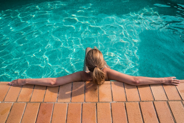 Mujer que se relaja en piscina azul al aire libre. vista trasera