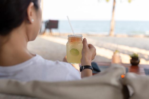 Mujer que se relaja en la playa con la bebida fresca de la miel del limón del vidrio de mano.