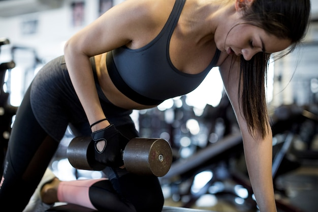 Mujer que se resuelve con pesa de gimnasia