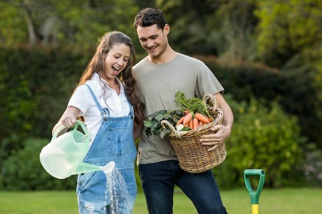 Mujer que riega plantas mientras que hombre que sostiene la cesta de verduras en jardín