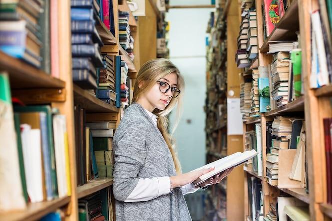 Mujer que se inclina en el estante para libros y que mira la cámara