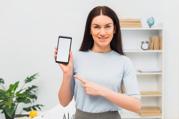 Mujer que señala el dedo en el teléfono inteligente con pantalla en blanco