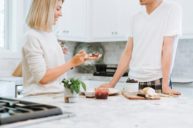 Mujer que separa el queso crema vegano en una tostada
