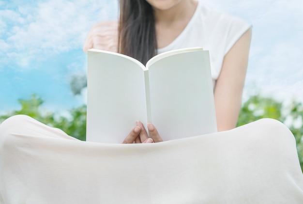La mujer que se sienta en campo en el jardín público para leer por la mañana, relaja el tiempo de la mujer asiática en el foco suave y selectivo