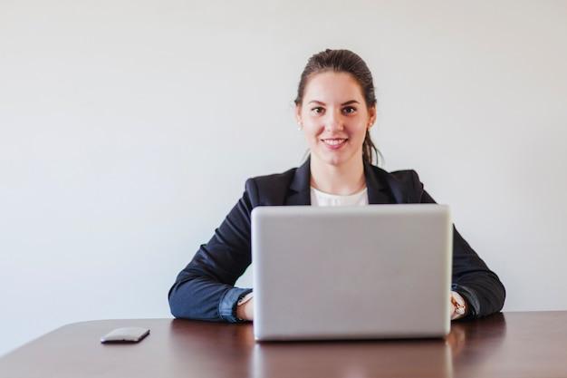 Mujer que se sienta en el escritorio que trabaja en la computadora portátil