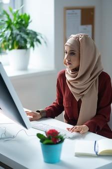 Mujer que se siente ocupada. mujer de ojos oscuros con pañuelo en la cabeza sintiéndose ocupada mientras trabaja sentado cerca de la computadora