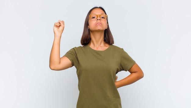 Mujer que se siente seria, fuerte y rebelde, levanta el puño, protesta o lucha por la revolución
