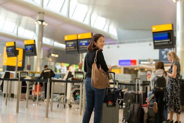 Mujer que sonríe con la mano que sostiene el pasaporte y la tarjeta de embarque en el aeropuerto internacional