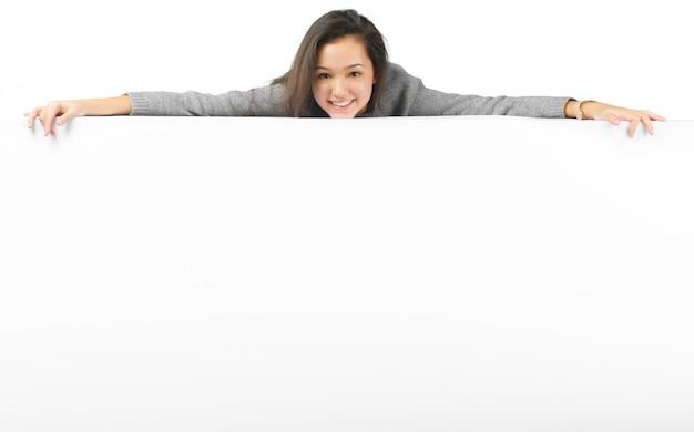 Mujer que sonríe mostrando la cartelera en blanco blanca de la muestra