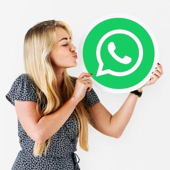 Mujer que sopla un beso a un ícono de whatsapp messenger