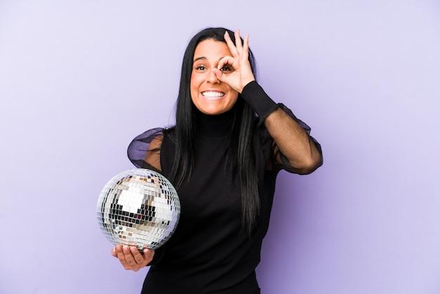 La mujer que sostenía una fiesta de la bola aislada en púrpura excitó guardar gesto aceptable en ojo.