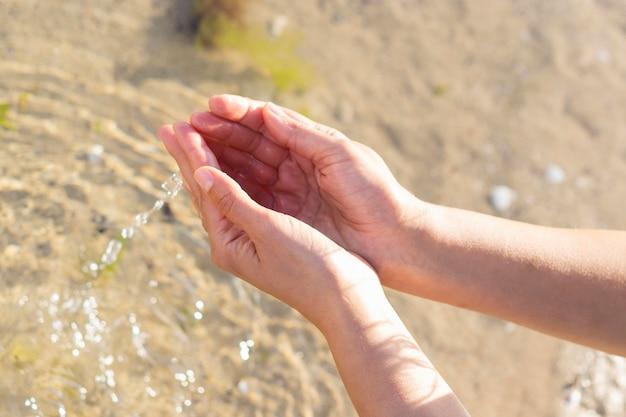Mujer que sostiene el agua clara en sus manos