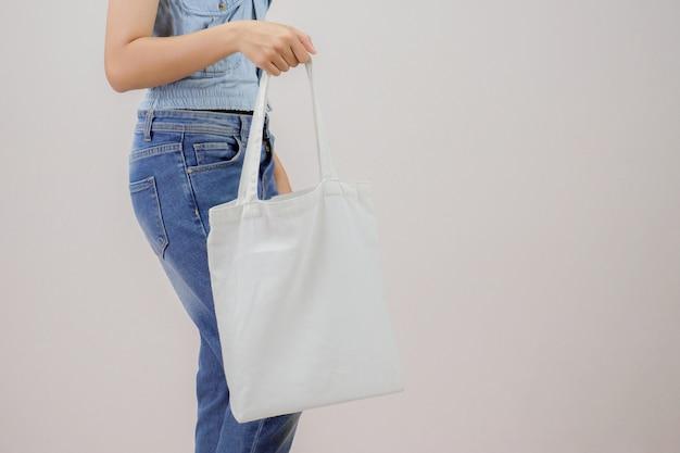 Mujer que sostiene el aislante del bolso de la tela del eco en fondo gris