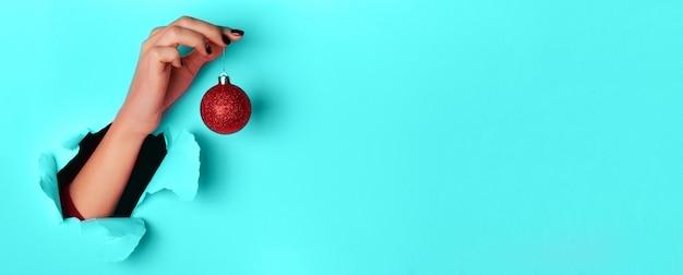Mujer que sostiene la bola de navidad roja brillante en la mano