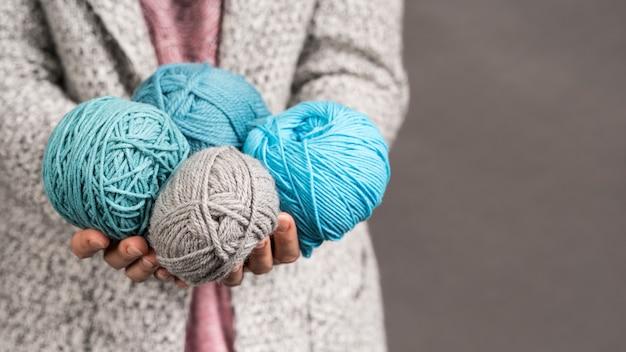 Mujer que sostiene bolas coloridas del hilado de lanas
