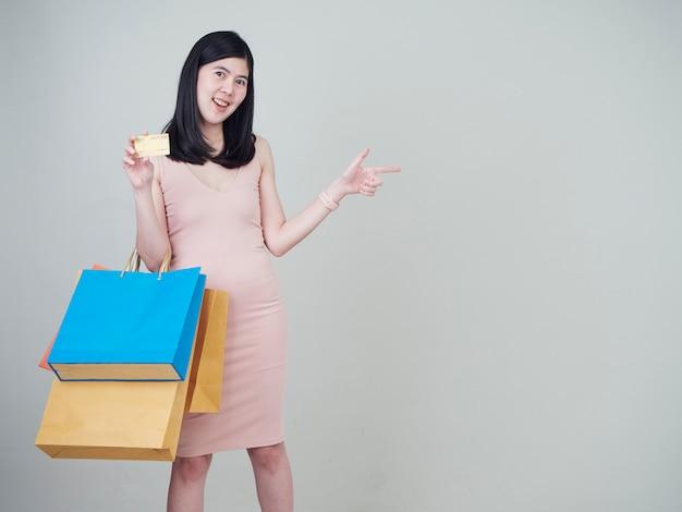 Mujer que sostiene el bolso de compras y las tarjetas de crédito