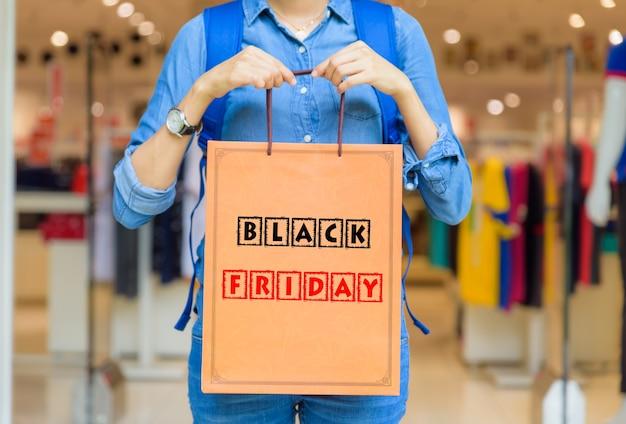 Mujer que sostiene bolsos de compras en la alameda de compras con el concepto de black friday.