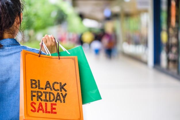 Mujer que sostiene bolsos de compras en el centro comercial con black friday words concept.