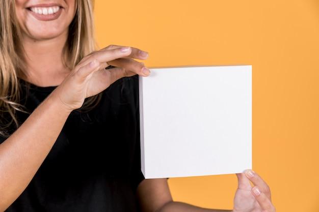 Mujer que sostiene la caja blanca en blanco delante de la superficie amarilla