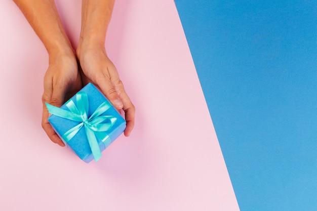 Mujer que sostiene la caja de regalo en color
