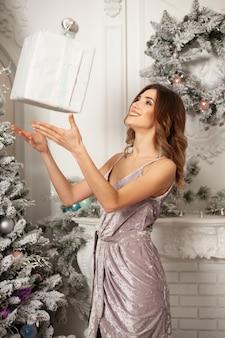 Mujer que sostiene la caja de regalo de navidad mágica.