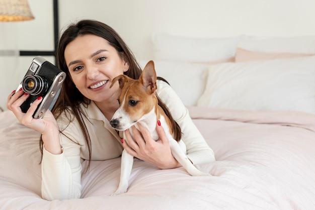 Mujer que sostiene la cámara y el perro en la cama