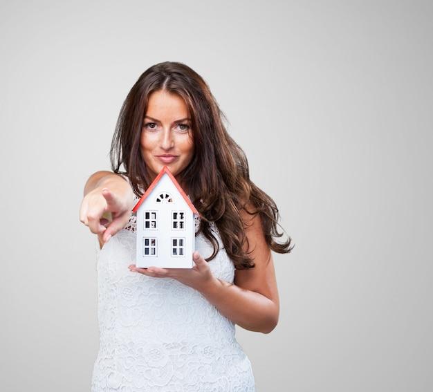 Mujer que sostiene una casa y apuntando hacia delante