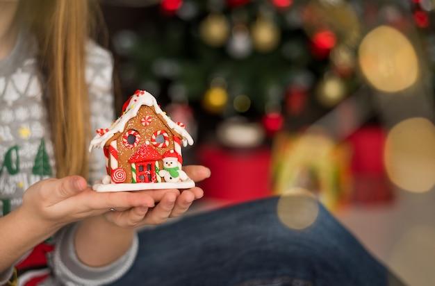 Mujer que sostiene la casa de pan de jengibre de navidad