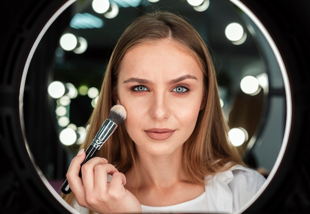 Mujer que sostiene el cepillo grande que mira el espejo Foto Premium