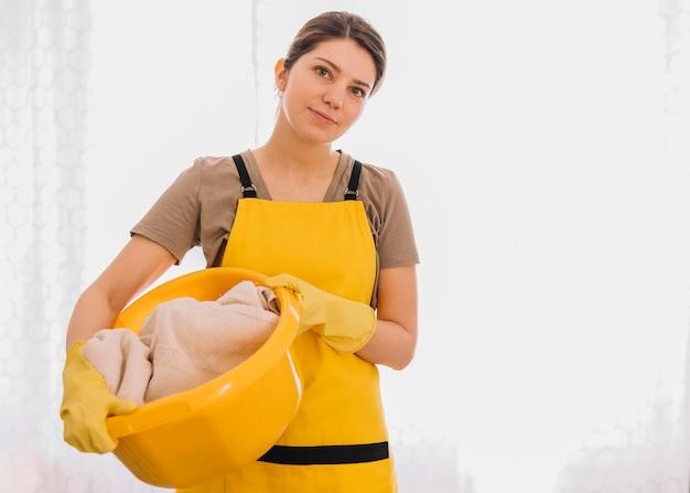 Mujer que sostiene la cesta amarilla