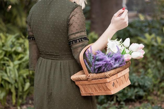 Mujer que sostiene la cesta con flores