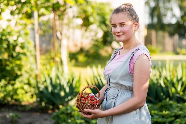 Mujer que sostiene la cesta de fresas