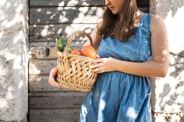 Mujer que sostiene la cesta con verduras