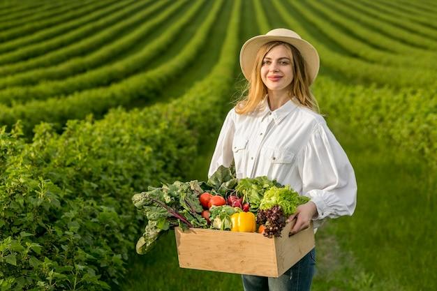 Mujer que sostiene la cesta de verduras