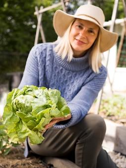 Mujer que sostiene una col verde