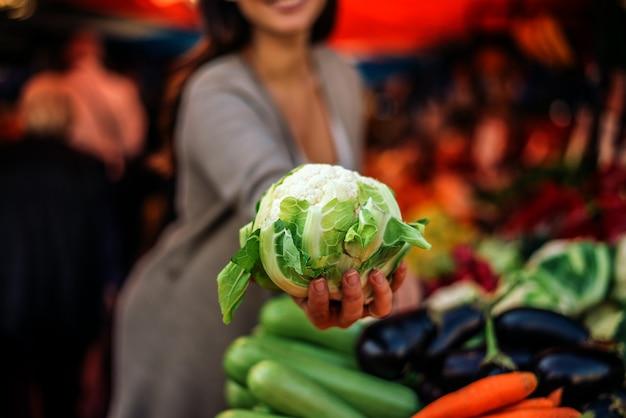 Mujer que sostiene la coliflor en el mercado de los granjeros.
