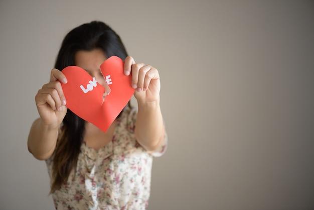 Mujer que sostiene el corazón roto rojo con el texto del amor. concepto de día de san valentín