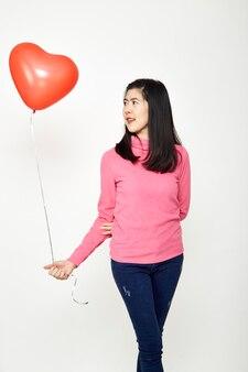 Mujer que sostiene el corazón rojo grande del globo