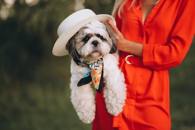 Mujer que sostiene el perro lindo en sus manos