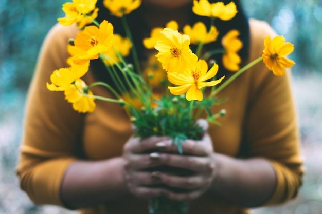 Mujer que sostiene la flor amarilla del cosmos en la mano